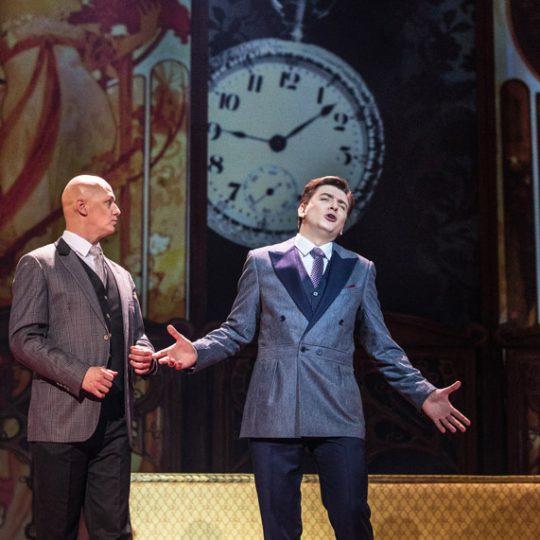 Dwóch elegancko ubranych mężczyzn stoi obok siebie. Jeden rozkłada szeroko ręce i śpiewa, drugi patrzy na niego.