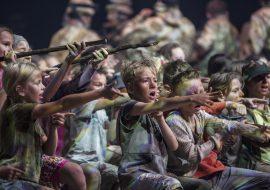 Na scenie grupa dzieci, w przybrudzonych ubraniach, z brudnymi twarzami. Trzymają wyciągnięte ręce do przodu, dwoje dzieci trzyma w dłoniach patyki.