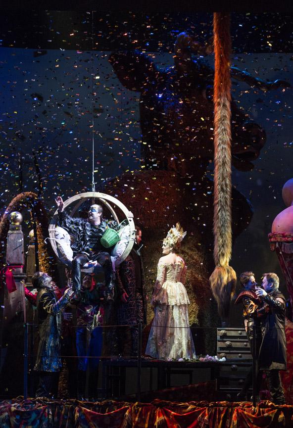 Na scenie kilka kobiet i mężczyzn. Po lewej stronie huśtawka w kształcie koła. W środku siedzi mężczyzna. Obok stoi kobieta w balowej sukni. Wszystko wypełnia spadające confetti.