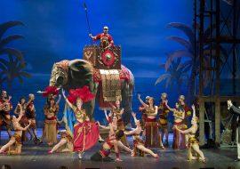 Scena wypełniona tancerzami w złoto-czeronych strojach. Wszyscy tańczą. Za nimi stoi duży słoń, na nim mężczyzna z włócznią. Po prawej trzech, elegancko ubranych mężczyzn klaszcze.