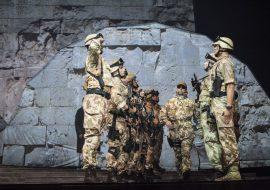 W dwóch rzędach mężczyźni w mundurach moro, zwróconych przodem do siebie. W środku mężczyzna w mundurze moro, idący w stronę widowni. W tle ściana z cegieł.