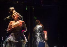 Na pierwszym planie kobieta w sukni wieczorowej. Za nią stoi mężczyzna, trzymając ją za biodra. Po prawej stronie duże lustro.