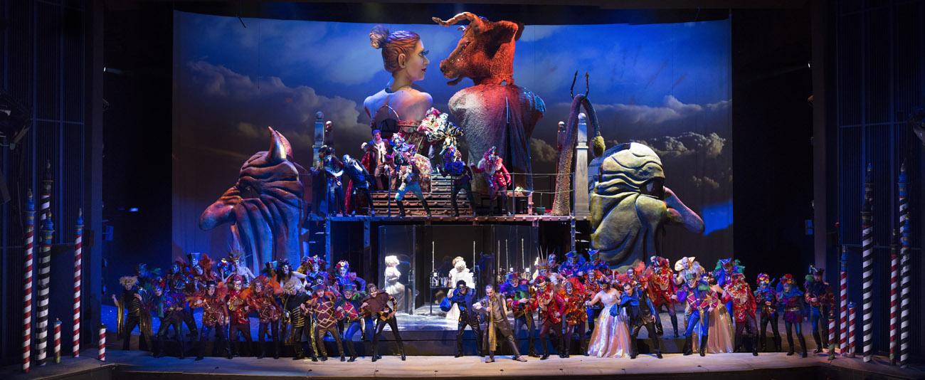 Na scenie kilkadziesiąt osób w kostiumach balowych. Za nimi , na podwyższeniu kilku mężczyzn. W tle duży tułów kobiety w gorsecie i mężczyzny w