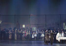 Po prawej stronie, przy stole stoi kilkunastu mężczyzn. Po lewej stronie kosz do gry w koszykówkę. Na nim siedzi mężczyzna ze skrzypcami. W oddali za wysoką siatką kilkadziesiąt kobiet.