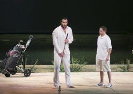 Na scenie dwóch mężczyzn. Jeden z nich trzyma kij do golfa. Obok niego stoi wózek golfowy z kijami. Za nimi staw.