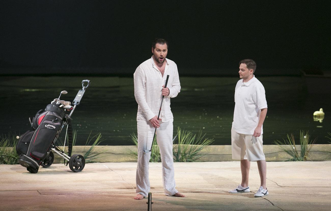 Na scenie dwóch mężczyzn. Jeden z nich trzyma kij do golfa. Obok niego stoi wózek