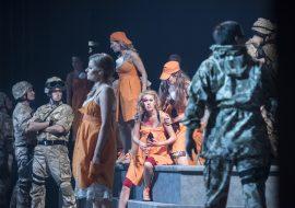 Na środku kilka kobiet w pomarańczowych fartuchach. Kilka z nich stoi, jedna siedzi na schodach. Wokół nich mężczyźni w mundurach moro.
