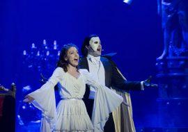 Ciemna scena oświetlona niebieskim światłem. Na środku kobieta w białej sukni i mężczyzna z maską na twarzy, ubrany w czarny frak i czarną pelerynę. Śpiewają z rękami rozłożonymi w bok.