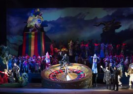 Na środku sceny duża ruletka. W środku siedzi mężczyzna. Po lewej stronie zielona wyspa, na niej kilka kobiet i mężczyzn. W oddali kilkadziesiąt osób w kostiumach lalkarskich. Za nimi , na kolorowym podwyższeniu - głowa klauna.