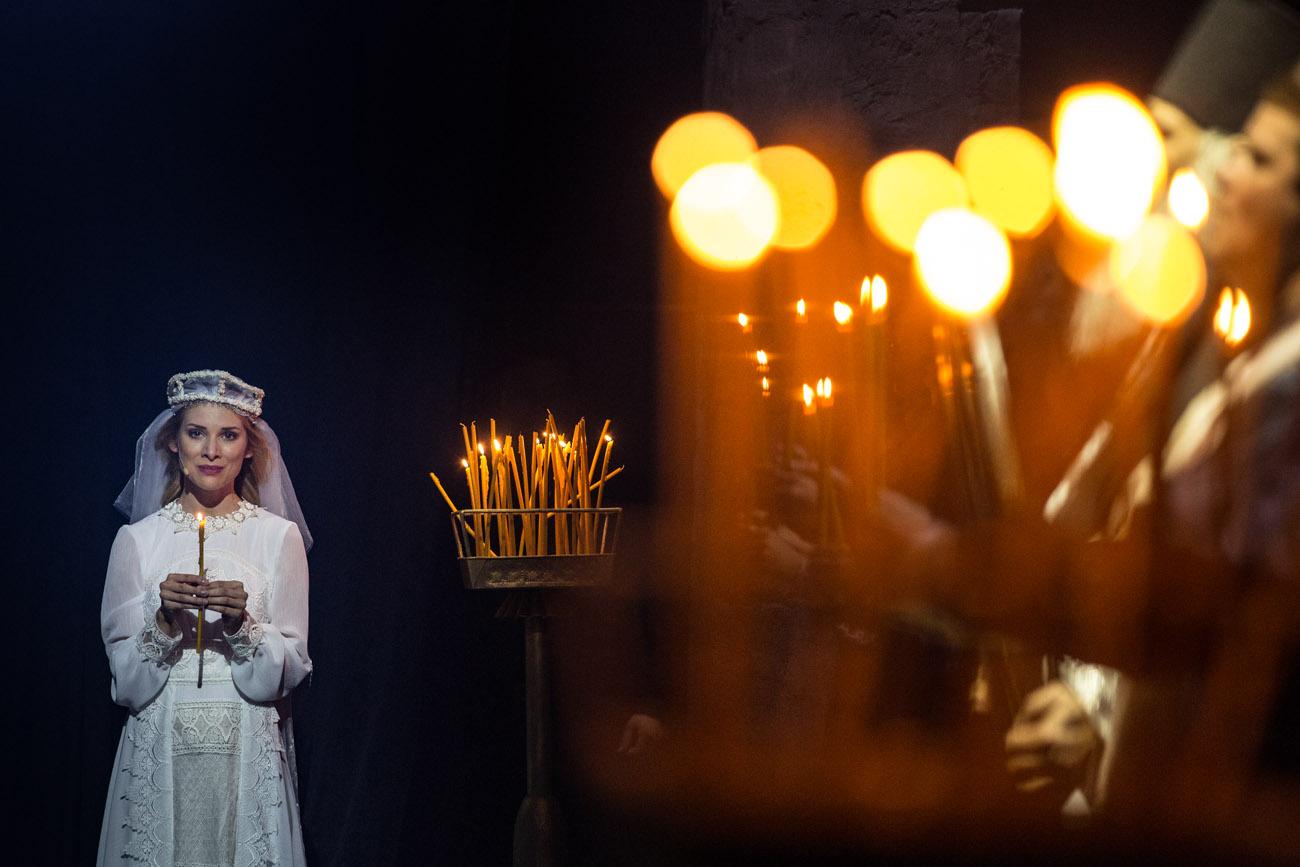 Na zdjęciu kobieta w białej, koronkowej sukience i w welonie. Trzyma w dłoniach zapaloną świeczkę. Na środku, na stojaku stoi kilkadziesiąt świeczek, część z nich pali się. Po prawej stronie w rozmytym tle, widać kilka osób trzymających zapalone świeczki.