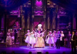 Na środku kilka kobiet w białych tiulowych sukienkach tańczy wokół kobiety w stojącej balowej sukni. Po obydwu stronach stoją kobiety i mężczyźni. Wszyscy śpiewją.