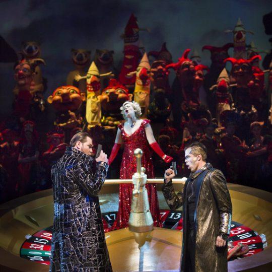 Na scenie duża ruletka. Na środku stoi kobieta w czerwonej, balowej sukni. Przed ruletką stoi dwóch mężczyzn, w długich płaszczach. Trzymaja w dłoniach pistolety. Za nimi kilkanaście osób w kostiumach lalkowych.