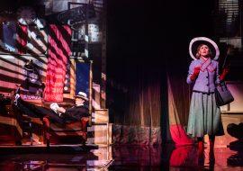 Po prawej stronie kobieta w szarym kostiumie. W kapeluszu i czerwonych rękawiczkach. Po lewej, na fotelu, leży mężczyzna w garniturze. Nogi trzyma na szafce. Za nim wyżej, stoi gitara.