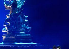 Scena oświetlona niebieskim światłem. Męzczyzna w czarnej pelerynie z maską na twarzy, w pozycji przykucniętej, trzyma czerwoną różę. Za nim pomnik anioła z lirą.