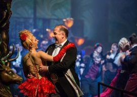 Kobieta w czerwonej sukience z czerwoną różą we włosach tańczy z mężczyzną w czarnym fraku. Obydwoje się śmieją. W tle tańczą inne pary.