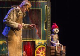 Po lewej stronie mężczyzna w długim skórzanym fartuchu, z maską na oczach. Obok, na drewnianej skrzynce siedzi drewniana lalka w spodniach w kratkę i w czerwonej czapce. Za nimi drewniany pojazd.