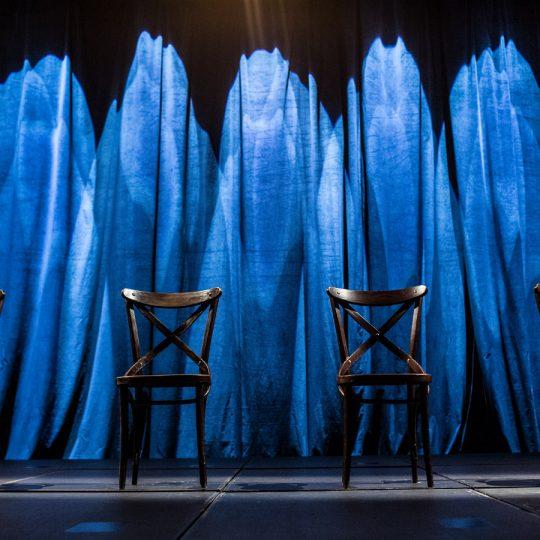 Na scenie cztery krzesła . Za nimi, podświetlona na niebiesko kotara.