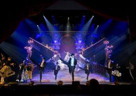 Na scenie duże schody. Na przodzie tańczą mężczyźni w czarnych frakach, za nimi kobiety w białych sukniach. Po bokach tańczą pary w karnawałowych kostiumach.