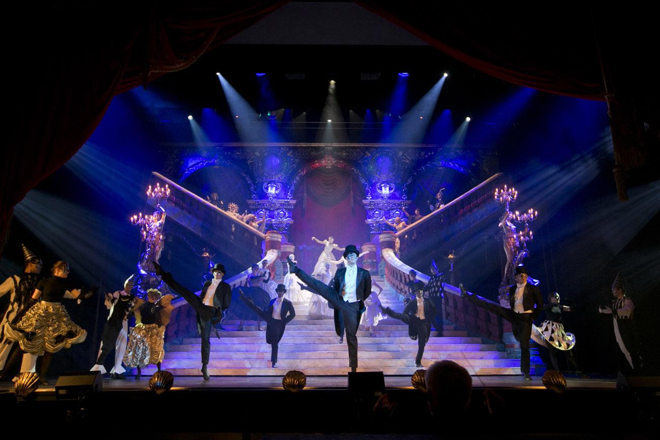 Na scenie duże schody. Na przodzie tańczą mężczyźni w czarnych frakach, za nimi kobiety w białych sukniach.Po bokach tańczą pary w karnawałowych kostiumach.