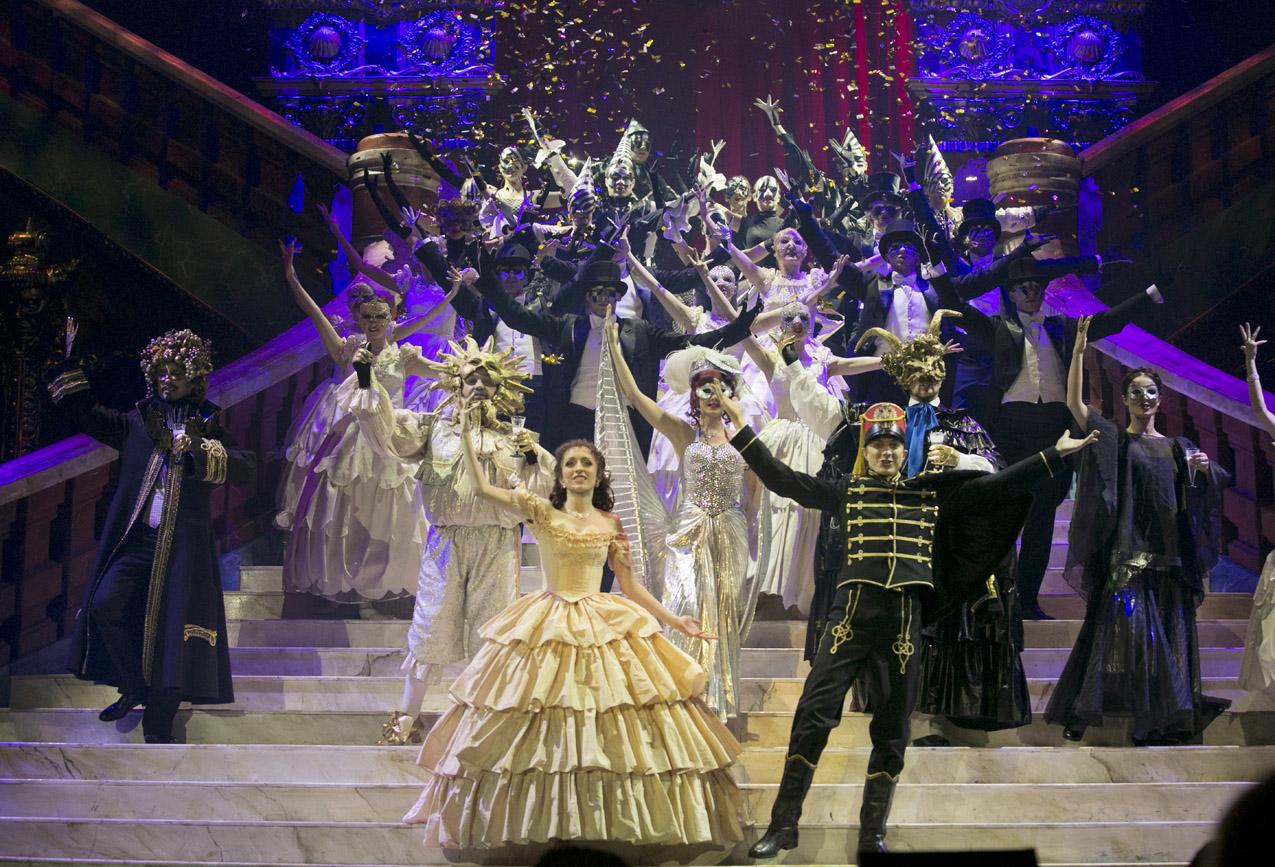 Na stopniach dużych schodów kilkanaście osób w strojach balowych, w maskach na twarzy. Wszyscy tańczą z rękoma uniesionymi ku górze. W tle - złote konfetti.