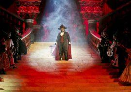 Scena oświetlona czerwonym światłem. Na środku dużych schodów stoi mężczyzna w czerwonym płaszczu i kapeluszu, z maską na twarzy. Po obydwu stronach, na stopniach schodów stoją kobiety i mężczyźni w balowych strojach.