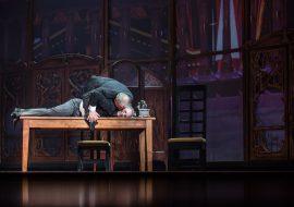 Mężczyzna leży brzuchem na stole, drugi mężczyzna pochyla się nad nim i coś mu mówi do ucha