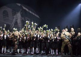 Na scenie grupa dzieci ubrana w galowe stroje, w podniesionych dłoniach trzymają białe kwiaty. Przed nimi, zwróconych przodem do nich, dwóch mężczyzn w mundurach moro, z karabinami. Po prawej stronie kilka kobiet w czarnych, długich sukniach. Na głowach mają hiszpańskie okrycia głowy - mantyle.