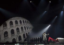 Po prawej stronie, na schodach leży kobieta w białej sukni. Ramię ma owiniętą czerwonym szalem. Po lewej stronie stoi mężczyzna z rękoma uniesionymi do góry. W oddali, w półmroku, grupa ludzi, oświetlona białym, punktowym światłem. Po lewej stronie część piętrowego budynku z oknami z balustradami.