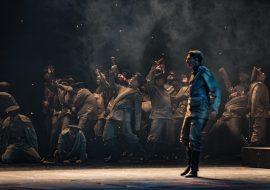Scena wypełniona dymem. Na niej kilkunastu mężczyzn w mundurach. Opadają na ziemię z podniesionymi rękoma. Na przodzie mężczyzna w mundurze stojący bokiem, patrzy przed siebie.