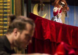 Na przodzie mężczyzna w czarnej koszuli, trzyma drewnianą lalkę. Dalej teatrzyk kukiełkowy. Na czerwonej zasłonie lalka teatralna.