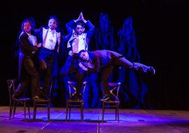 Scena oświetlona niebieskim światłem. Na środkowym kadrze czterech mężczyzn we frakach, stojących na krzesłach. Jeden z nich, pochylony do przodu, z podniesioną nogą do góry, opiera się na biodrze drugiego, stojącego na jednej nodze, z rękoma złożonymi nad głową.