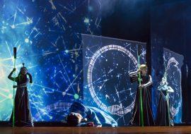 Na scenie stoją trzy postacie w czarnych, długich kostiumach. Trzymają w rękach długie podświetlone na zielono tyczki. Przed nimi leży mężczyzna w niebieskim ubraniu. Z tyłu iluminacja świetlna w postaci linii, kół i kropek.Po prawej stronie iluminacja przedstawiająca węża zwiniętego w koło.