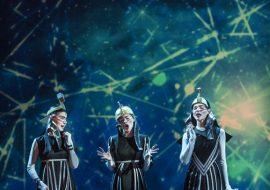 Trzy osoby w ciemnych , kostiumach stoją na scenie. Wszystkie śpiewają. Przed nimi leży człowiek w niebieskim ubraniu. Za nimi , na niebieskim tle, iluminacja świetlna w postaci, linii, kropek, kół.