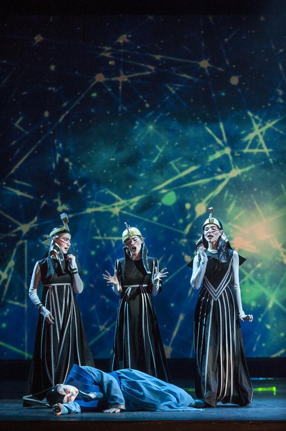 Trzy osoby w ciemnych , kostiumach stoja na scenie. Wszystkie śpiewają. Przed nimi leży człowiek w niebieskim ubraniu.. Za nimi , na niebieskim tle, iluminacja świetlna w postaci, linii, kropek, kół.