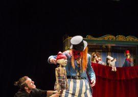 Na drewnianej scenie dwie skrzynki. Obok nich mężczyzna, w czarnej koszuli i spodniach, przytrzymuje lalkę z drewna. Obok stoi mężczyzna w spodniach w niebieskie paski, niebieską, krótką marynarkę. Pomarańczowe , długie włosy i czarny melonik. Trzyma drewnianą lalkę. Za nimi teatrzyk kukiełkowy. Na górze, na sznurkach wisi szyld z napisem: ''TEATRO MAGICO''
