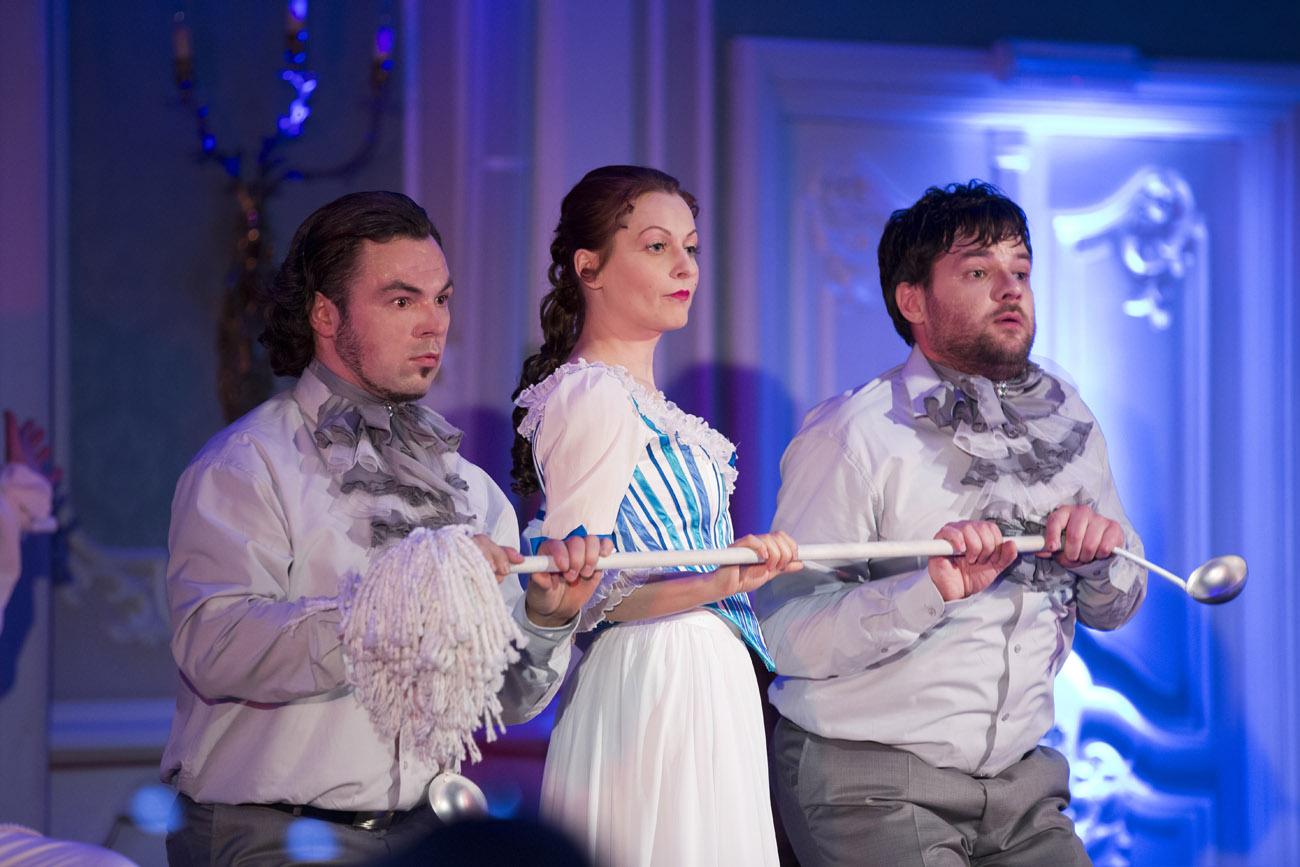 Kobieta w stroju pokojówki i dwóch mężczyzn po bokach, trzymają długą chochlę.