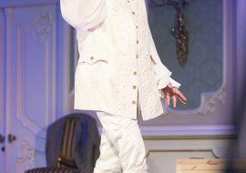 Na scenie stoi mężczyzna ubrany na biało, w białej peruce z długimi lokami. Trzyma dłoń przy twarzy mówiąc coś.
