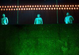 Na zdjęciu mur. Z góry zwisają dwie liny. Pomiędzy nimi stoi trzech mężczyzn. Na górze świecą dwa rzędy lamp.