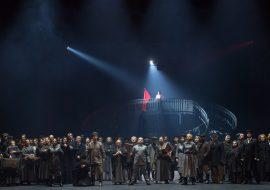 Na scenie kilkadziesiąt osób.Kobiety i mężczyźni. Stoją w rzędzie. Kilkoro z nich trzyma walizki. Jeden z nich klęczy. Za nimi wysokie schody, na nich stoi mężczyzna z flagą w kolorze czerwonym.
