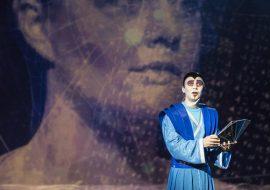 Na środku stoi mężczyzna ubrany w niebieski, długi kostium. Za nim widać duży portret kobiety.