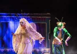 Na scenie dwie osoby, po lewej stronie kobieta w koronkowej sukience, w koronkowym welonie i białej masce na oczach. Po prawej stronie kobieta w zielonych, atłasowych spodniach i fraku. Na twarzy ma zieloną maskę z czułkami. Ręce wyciągnięte przed siebie, wygięte do wewnątrz. Za nimi drewniany pojazd.