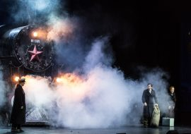 Scena wypełniona dymem. Po lewej stronie parowóz. Przed nim mężczyzna w czarnym płaszczu. Po prawej stronie kobieta z walizką i mężczyzna z dużym workiem.