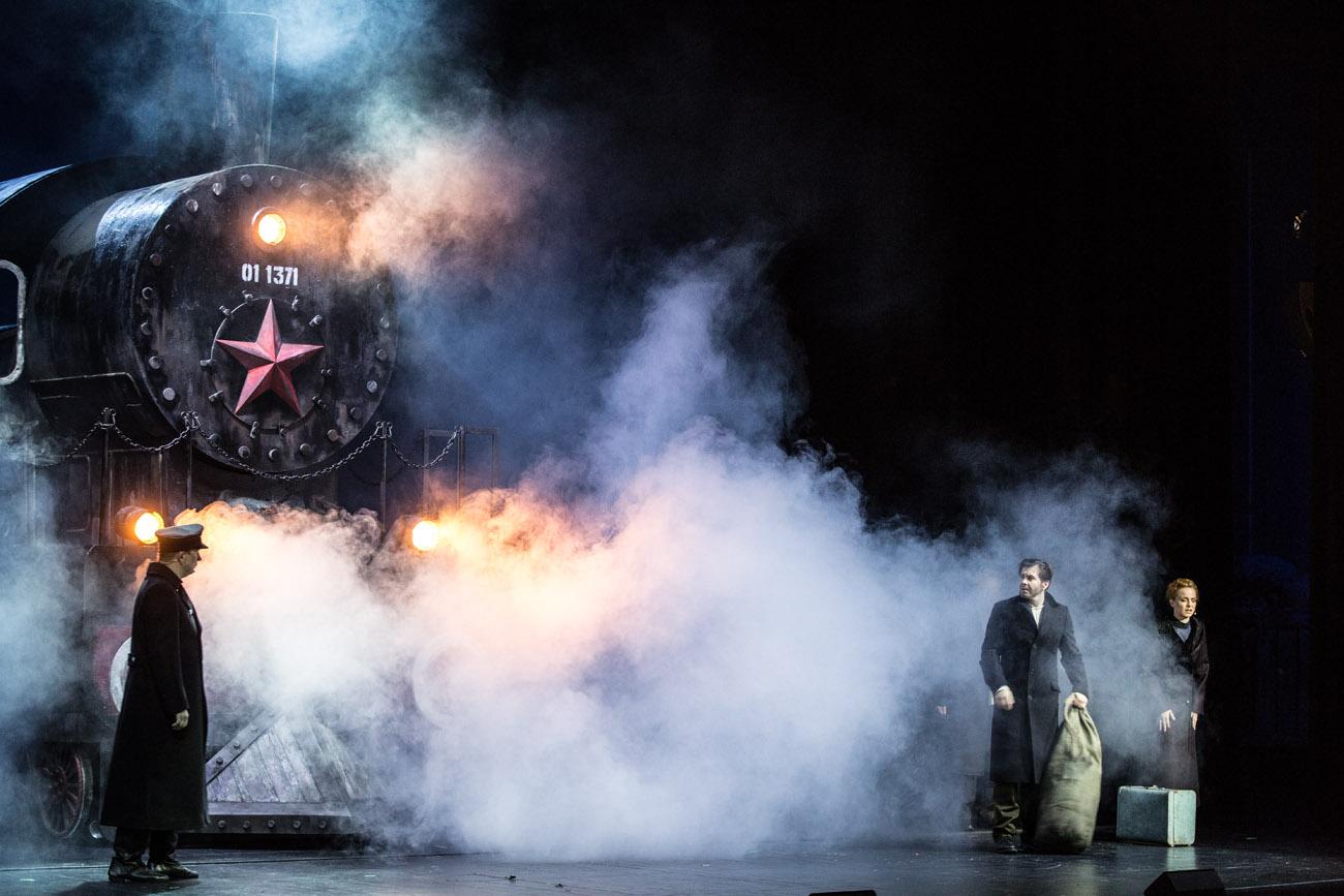 Scena wypełniona dymem. Po lewej stronie parowóz.Przed nim mężczyzna w czarnym płaszczu. Po prawej stronie kobieta z walizką i mężczyzna z dużym workiem.