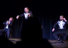 Trzech mężczyzn we frakach na scenie. Dwóch siedzi na krzesłach z ułożonymi rękoma imitującymi grę na instrumencie. Pośrodku męzczyzna stoi na krześle, z uniesionymi rękoma imitującymi grę na skrzypcach.