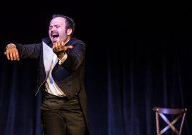 Mężczyzna we fraku trzyma uniesione ręce imitujące grę na skrzypcach. Za nim stoi krzesło.