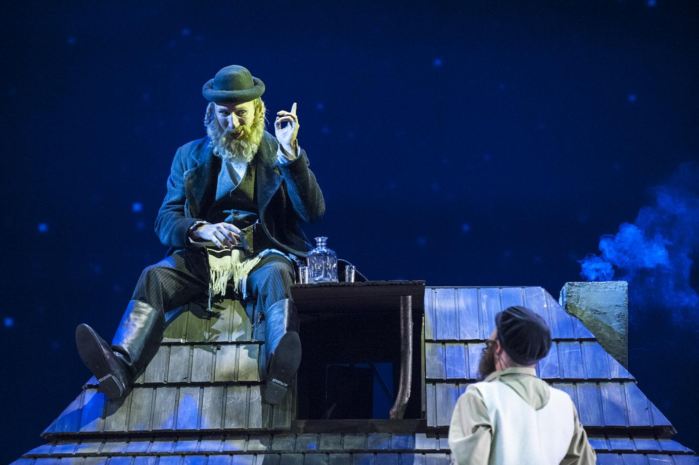 Na dachu małego domu siedzi mężczyzna z brodą w kapeluszu, trzymając rękę z palcem wskazującym do góry. Przodem do niego stoi mężczyzna z brodą w czapce, słuchając go. Z komina leci dym.