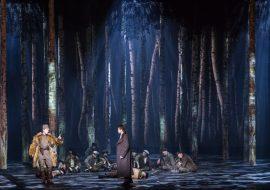 Scena słabo oświetlona. Dookoła drzewa. Pośród nich siedzi kilkunastu mężczyzn. Przed nimi, po prawej stronie mężczyzna w płaszczu. Po lewej - mężczyzna w futrze, trzyma palec wskazujący uniesiony do góry.