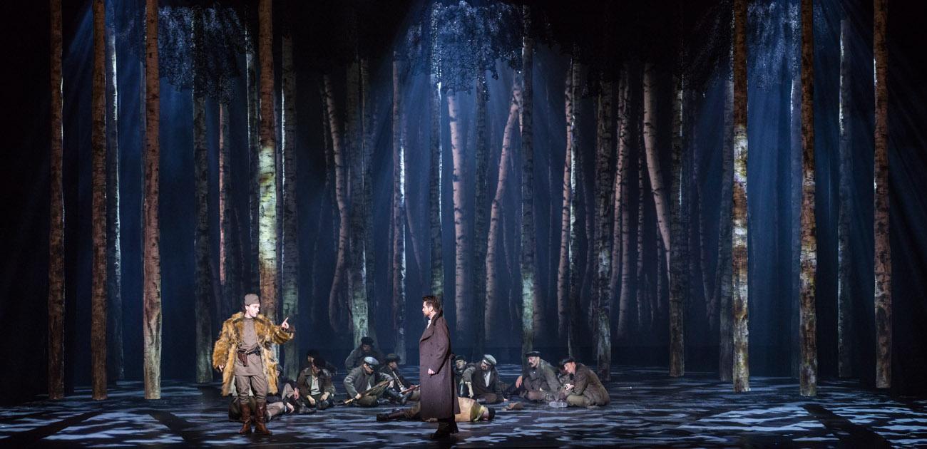 Scena słabo oświetlona. Dookoła drzewa. Pośród nich siedzi kilkunastu mężczyzn. Przed nimi, po prawej stronie mężczyzna w płaszczu. Po lewej - mężczyzna w futrze.