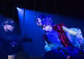 Ciemna scena oświetlona niebieskim światłem, dwaj mężczyźni przebrani za czarnego i kolorowego ptaka rozmawiają na kolanach. Czarny wyciąga rękę na znak zgody.