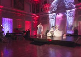 Scena w oddali. Na niej mężczyzna w ubraniu kobiety.Za nim siedzi para, mężczyzna pochylony w stronę kobiety w białej sukni. Po lewej stronie zespół muzyczny.